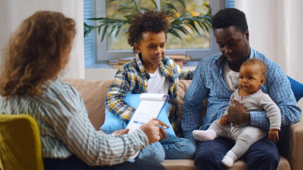 Social worker consulting smiling young single father with kids at home.